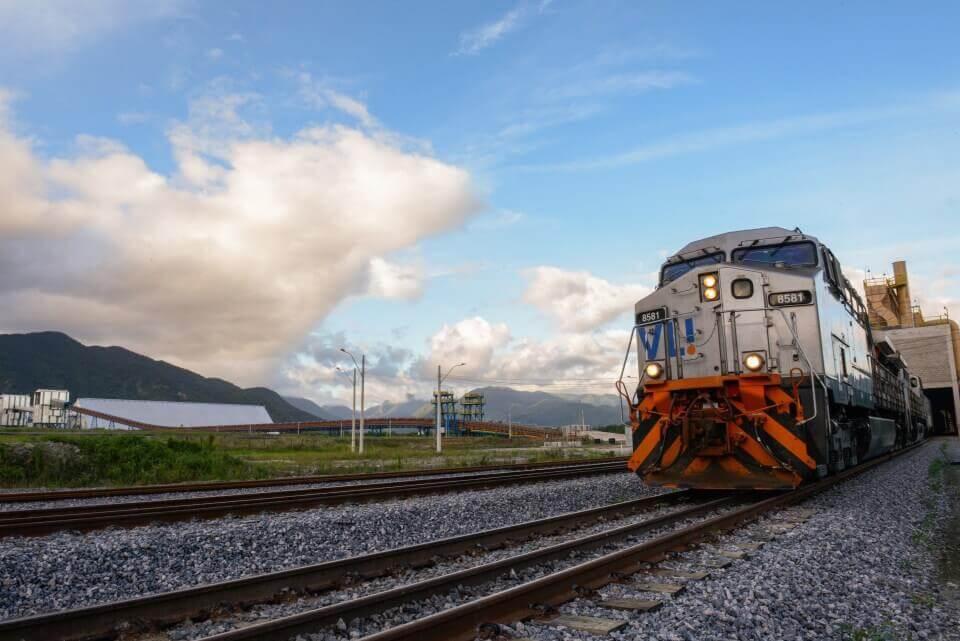 A frente de uma locomotiva da Ferrovia Norte Sul, estacionado em seus trilhos com o cenário natural local ao fundo, uma grande obra Ciser, de ponta a ponta