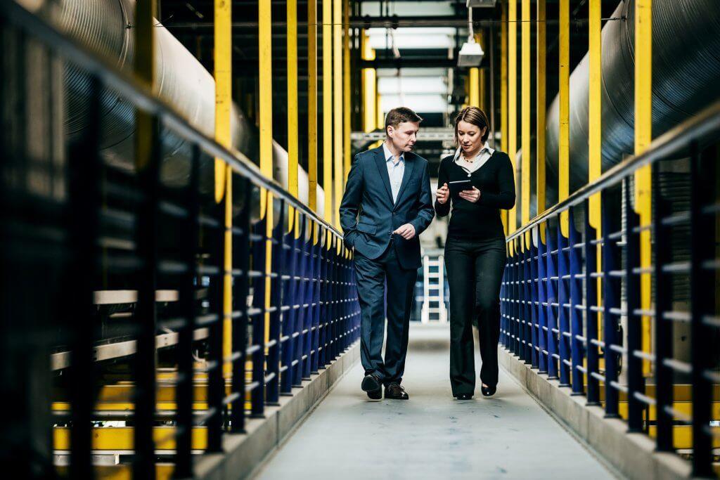imagem mostra dois homens caminhando na fabrica