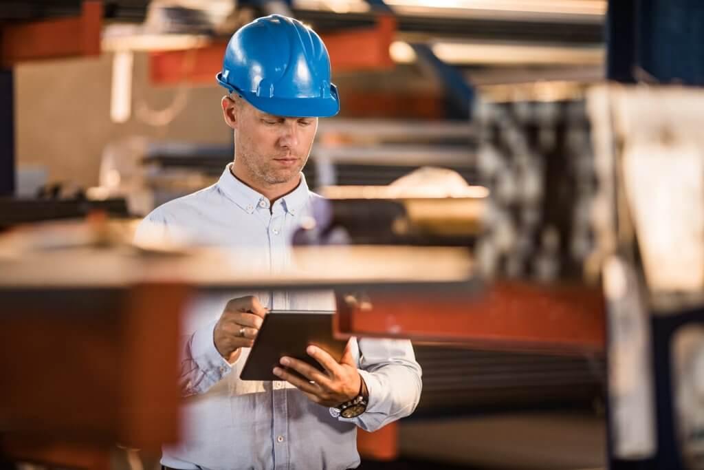 Engenheiro da indústria averiguando as certificações de qualidade no chão de fábrica