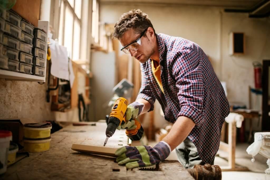 Homem em uma oficina, com óculos e luvas de proteção, utilizando uma furadeira para perfurar um pedaço de madeira.
