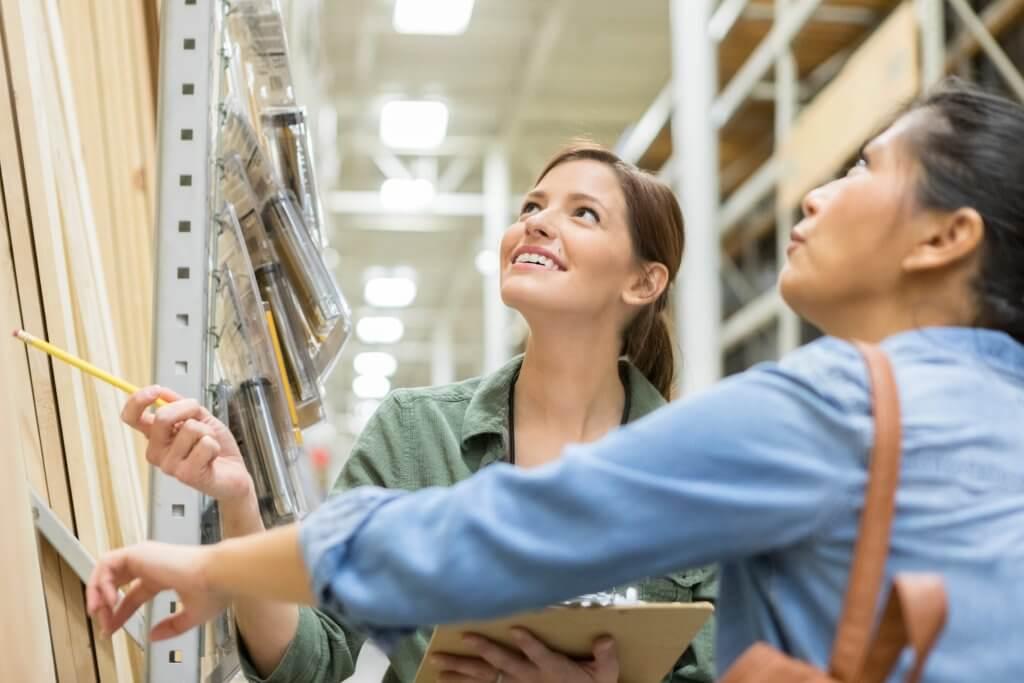 Uma alegre funcionária de uma loja de materiais de construção, adulta média, está de pé com uma prancheta e aponta para um item em uma prateleira. Ela ergue os olhos enquanto seu cliente estuda o produto.